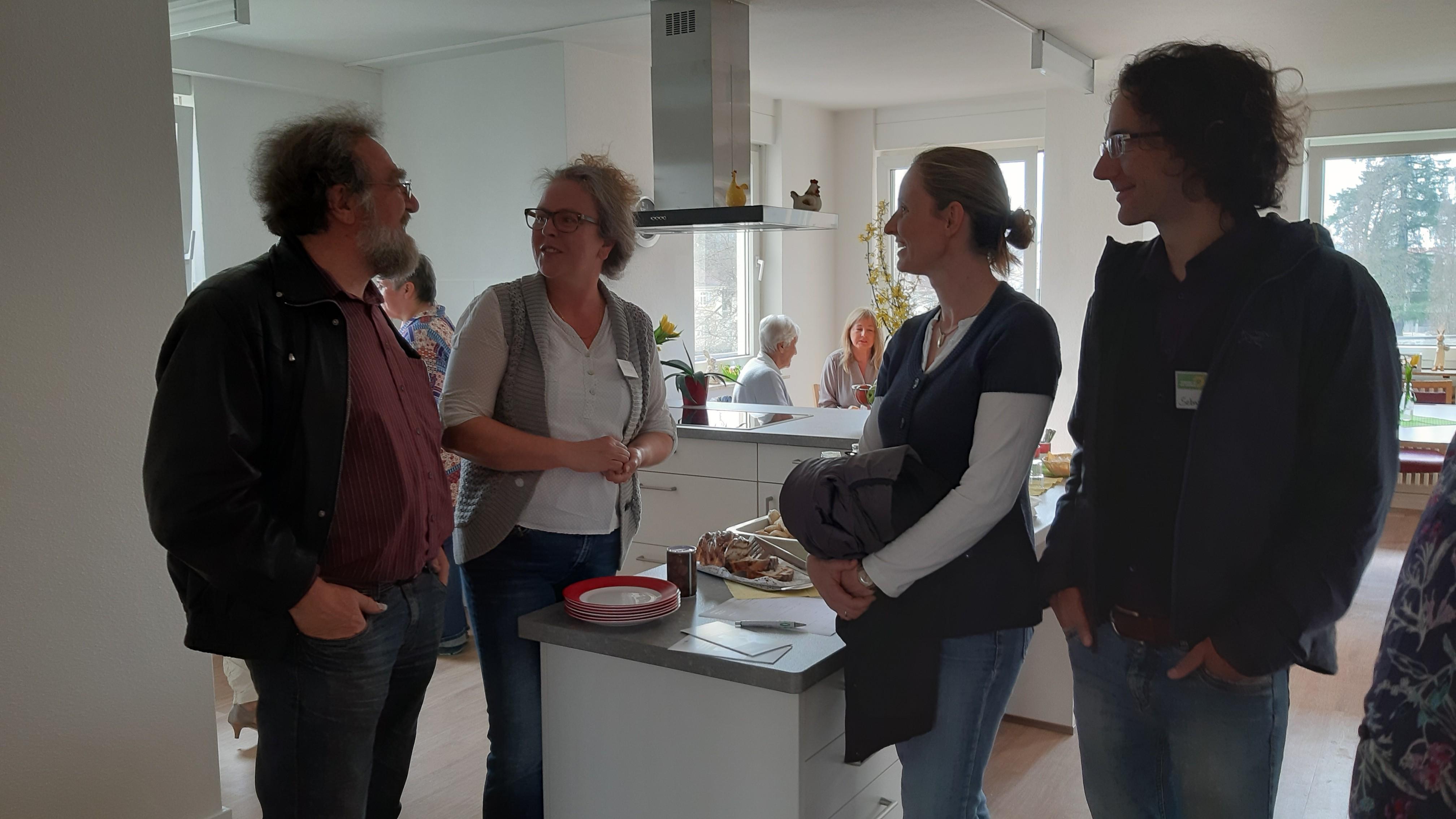 Herr Straub, Frau Merschhemke und Herr Prigge Im Gespräch mit einer Alltagsassistentin in einer Gemeinschaftsküche des Seniorenhauses Schopfheim